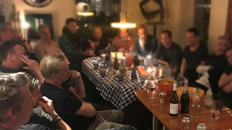 Ett stort gäng män sitter runt ett bord