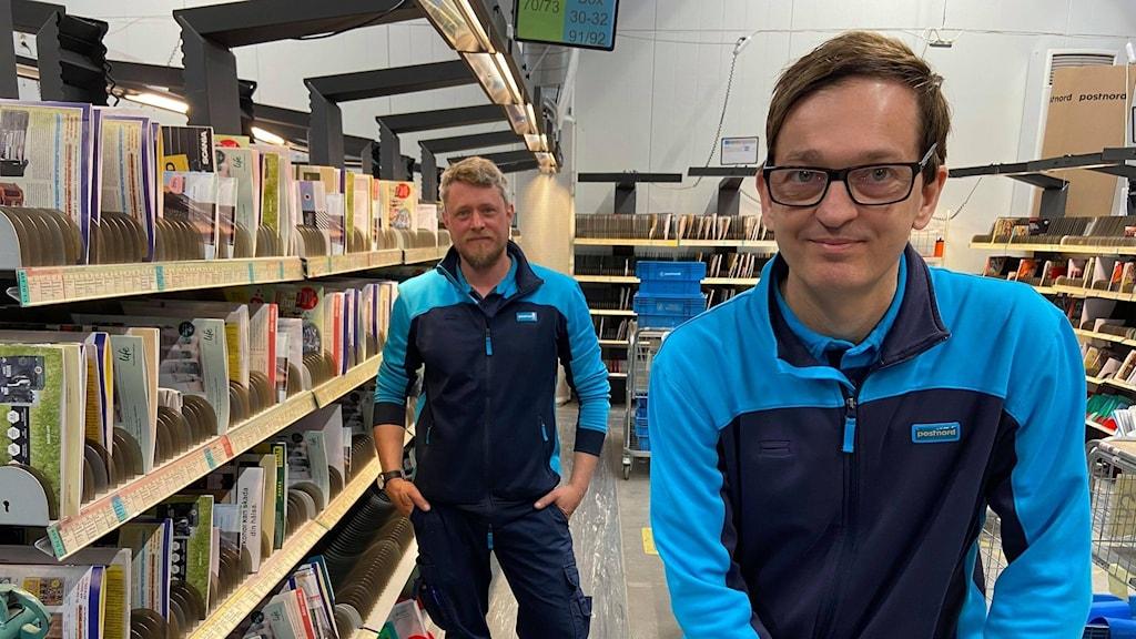 Bild på postkontoret. Stefan Johansson som är chef för Postnord i Uddevalla och Daniel johansson som är brevbärare tittar in i kameran. de ser glada ut.