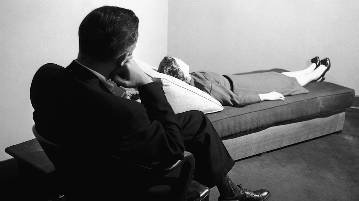 En man sitter på en stol och lyssnar på en kvinnlig patient som ligger på en säng