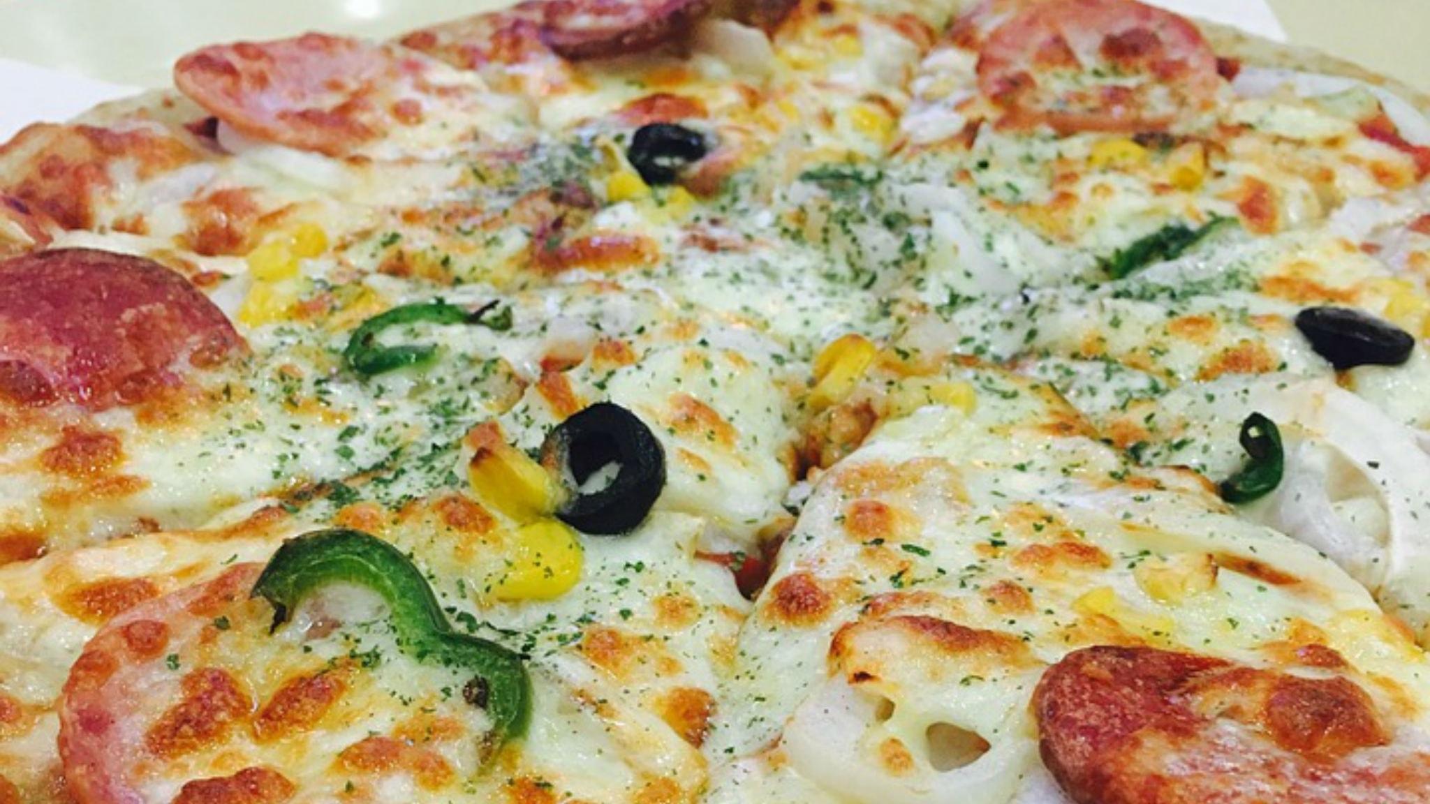 Pizza med ost och salami och oliver och paprika