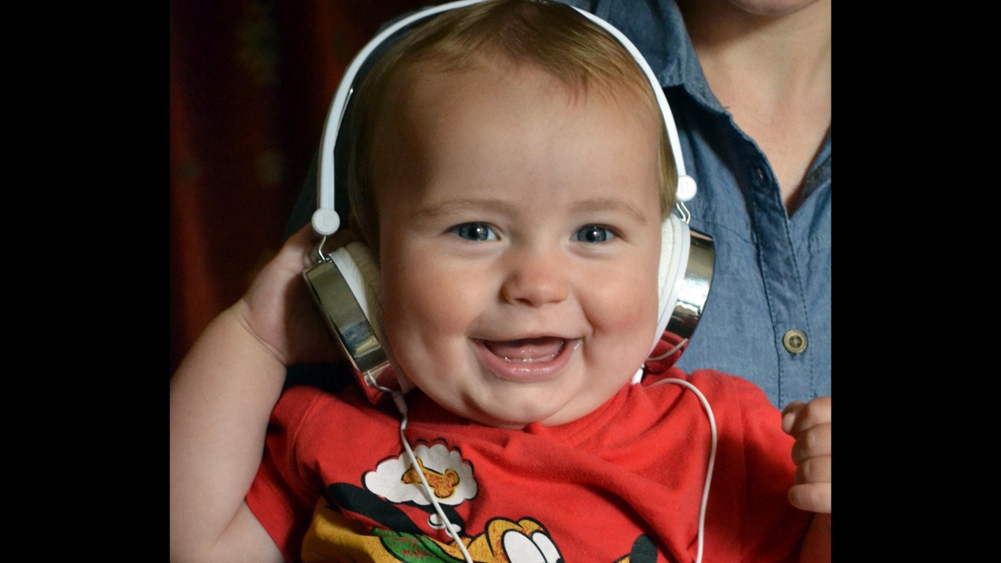 Bebis som lyssnar på musik i hörlurar