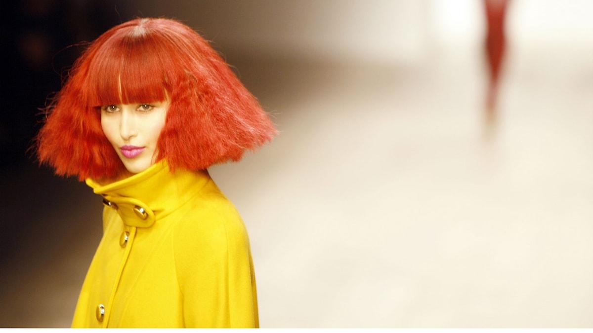 Kvinna rött hår gul kappa