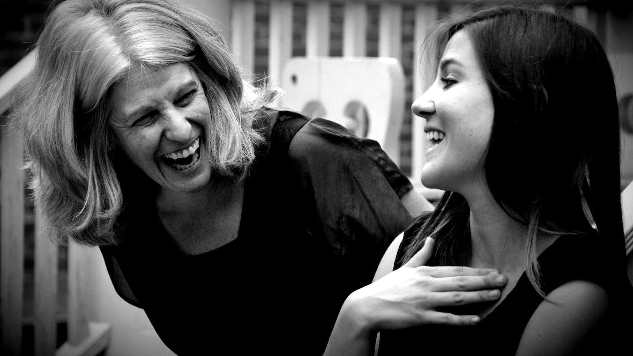 Två kvinnor som tittar på varandra och skrattar