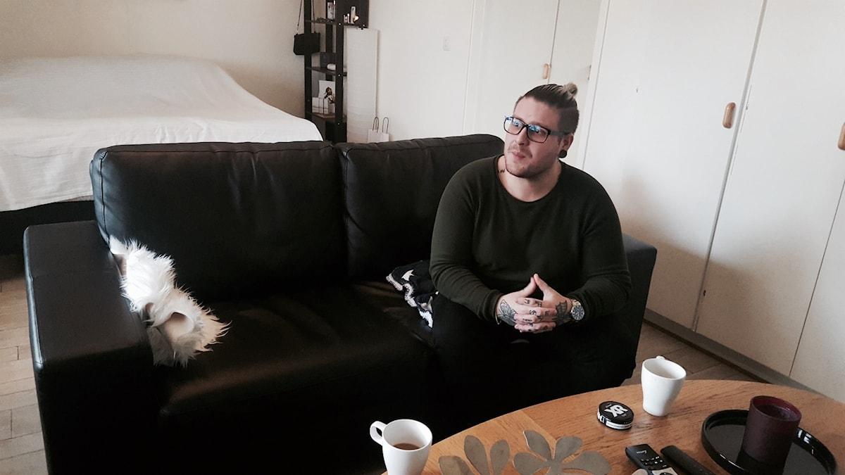 Alec sitter i en svart soffa. han har kämpat mot sin övervikt så länge han kan minnas.