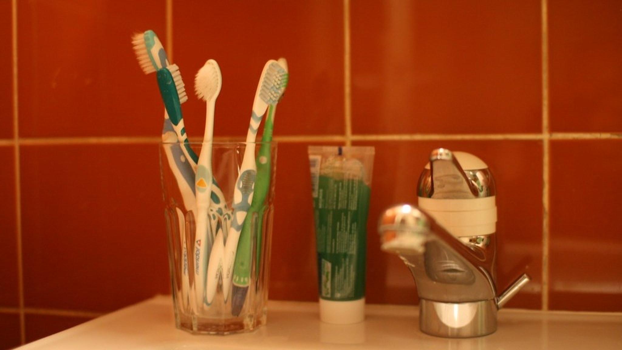 Tandborstar som står i ett glas på ett handfat