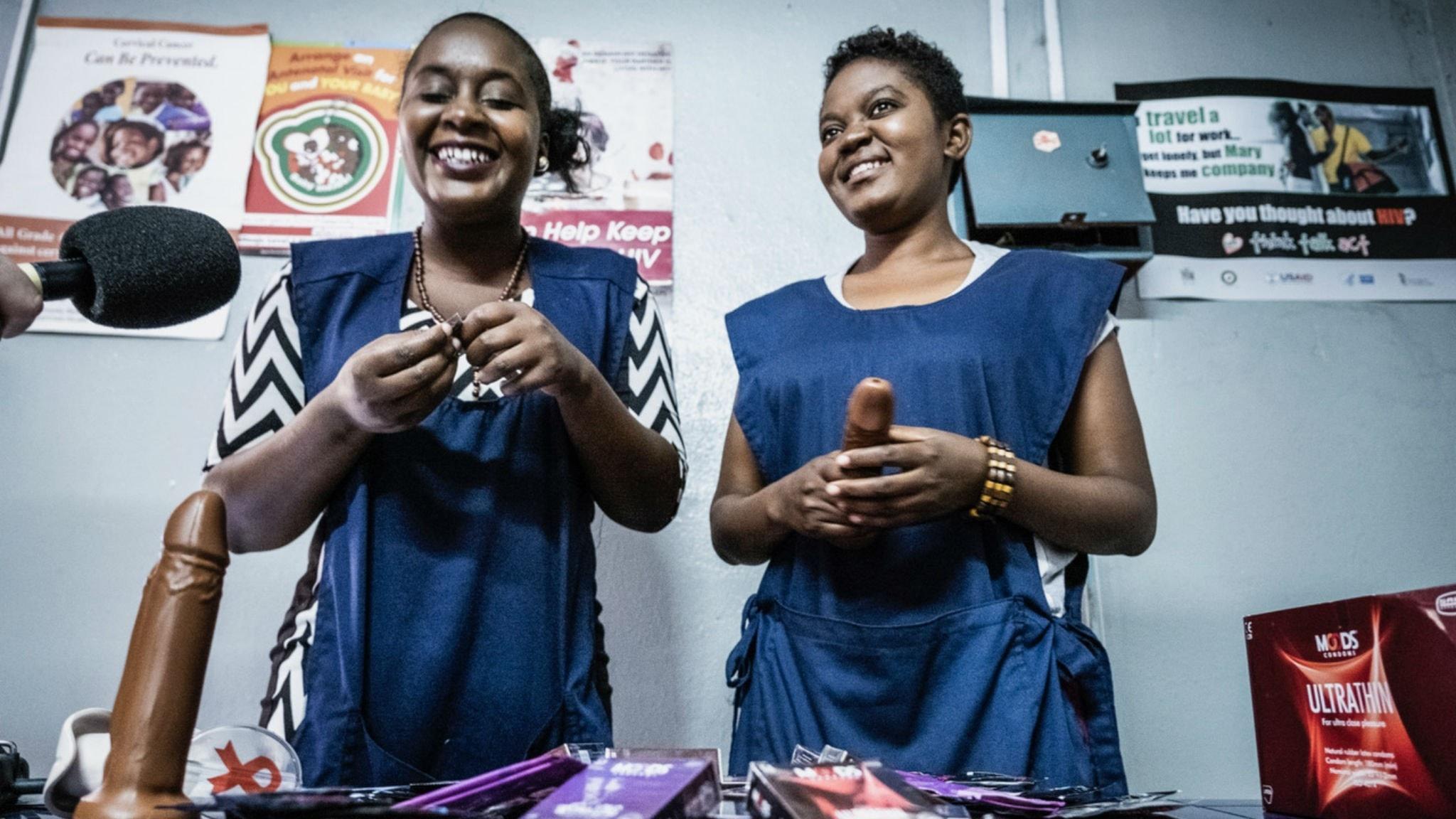 Två peer supporters i färd med att demonstrera hur man sätter på en kondom på en penisattrapp.