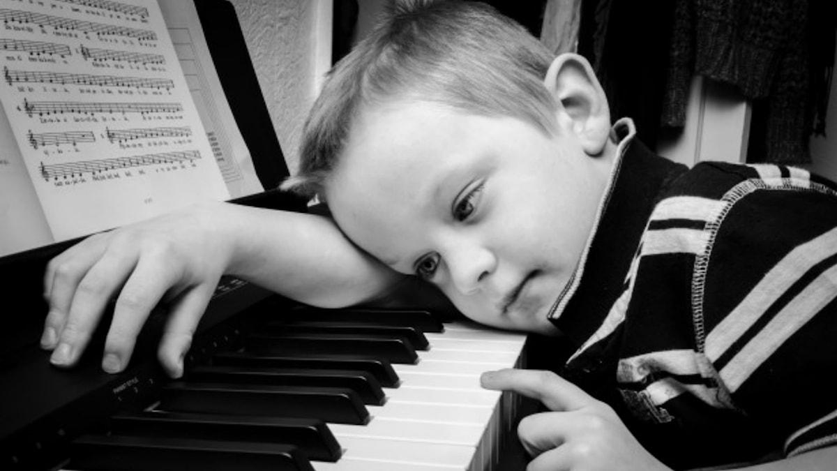 Pojke hänger över pianotangenter
