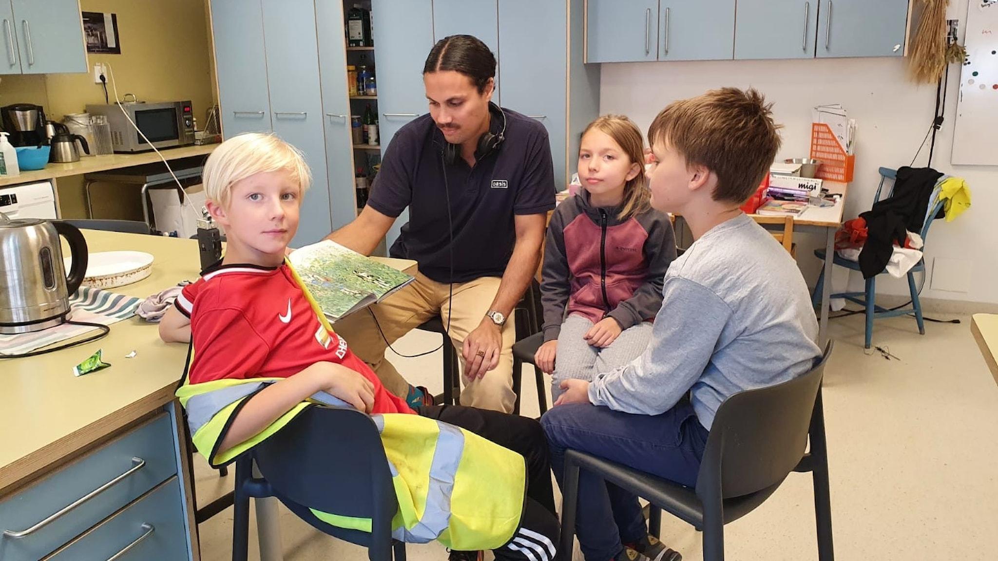 Reporter Sebastian sitter med tre barn och läser en saga