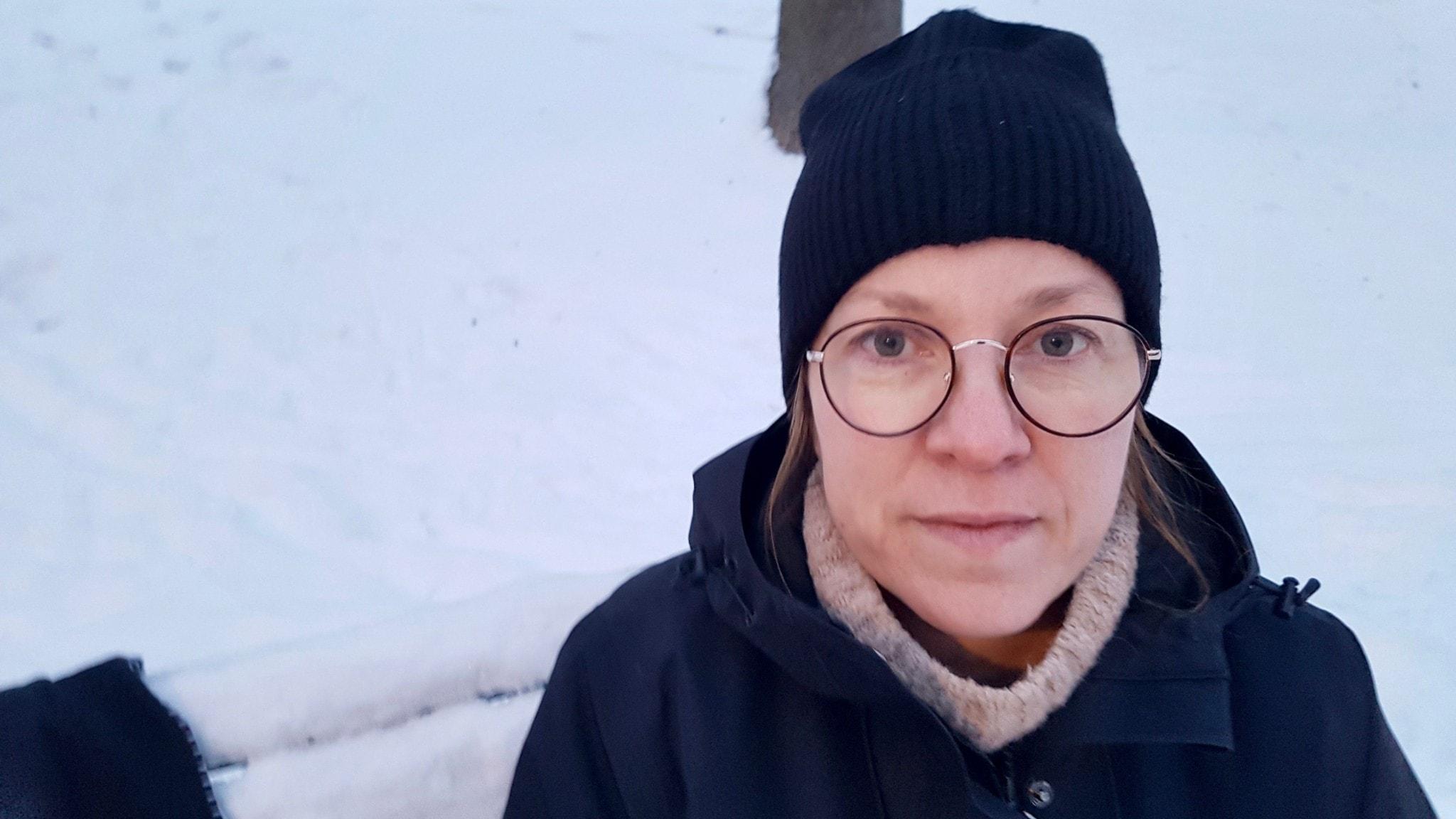 Kvinna i glasögon och ytterkläder tittar rakt in i kameran