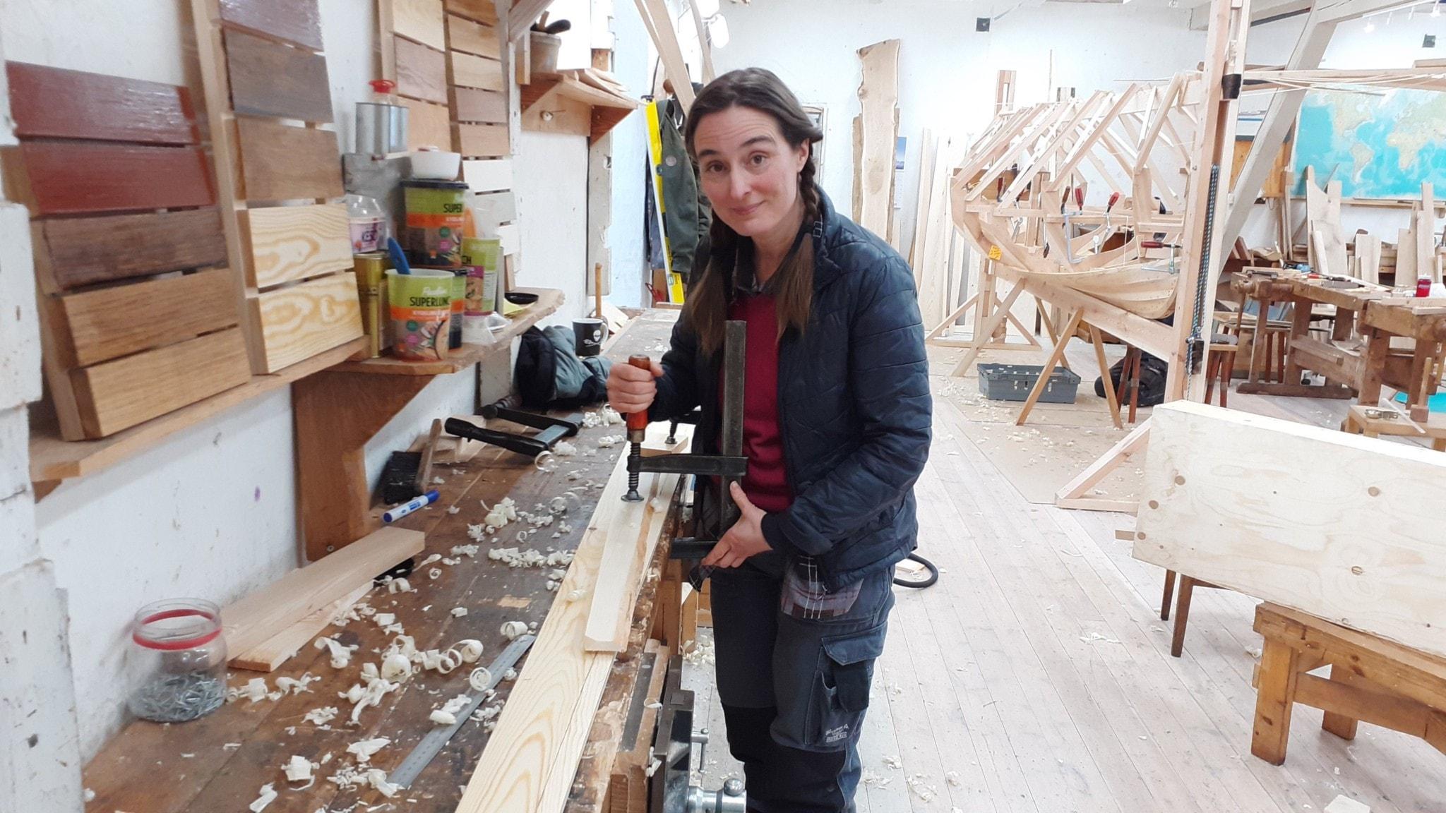 Lena Edlund står vid en arbetsbänk i båtverkstaden
