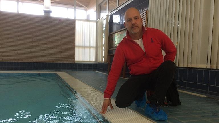 Fredrik Martell, vice ordförande för simklubben Stimmet sitter i simhallen i Laholm. Foto: Muhamed Ferhatovic/Sveriges Radio