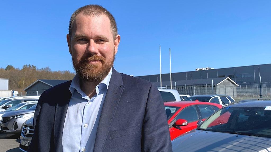 En man framifrån leendes in i kameran i bakgrunden syns bilar till salu. Utomhusmiljö.
