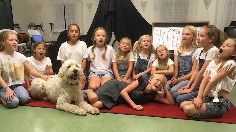 Ett tiotal barn sitter på golvet, tillsammans med en hund, och sjunger.