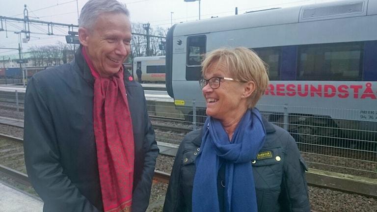 Ann-Charlotte Stenkil och Dag Hultefors står framför ett öresundståg på en tågstation.