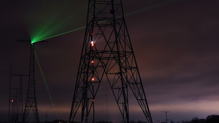 En grön laserstråle lyser från en radiomast.