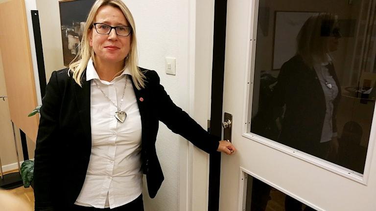 En kvinna står vid en dörr inomhus. Hon håller i dörrhandtaget och tittar in i kameran.