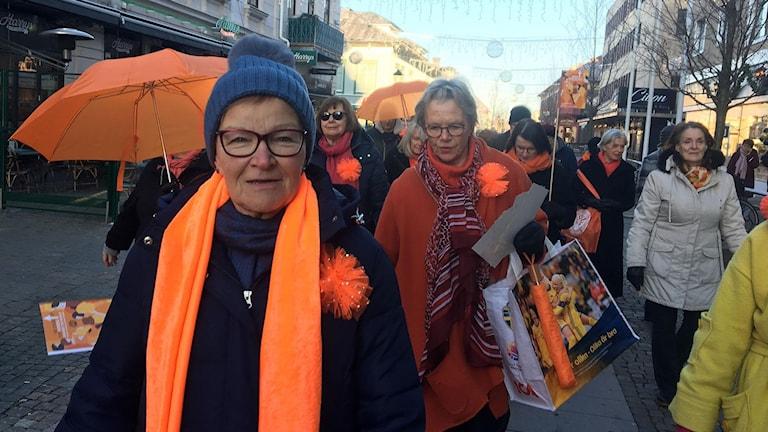 Längst fram syns Inger Svensson. I Bakgrunden syns flera kvinnor klädda i orange.