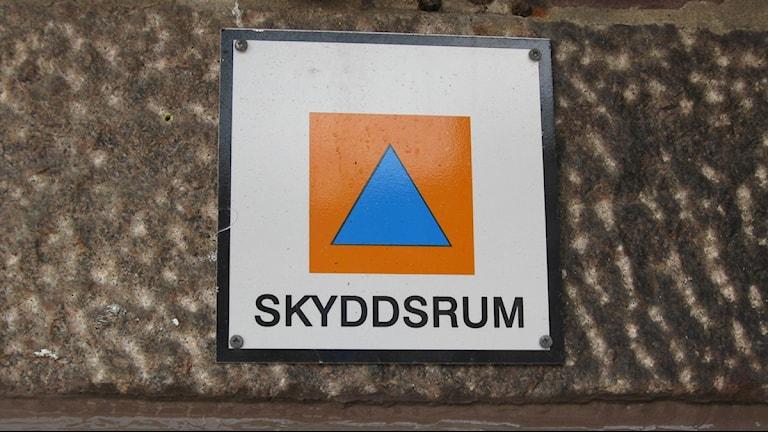 Skyddsrumssymbolen, en orange kvadrat med en blå triangel i.