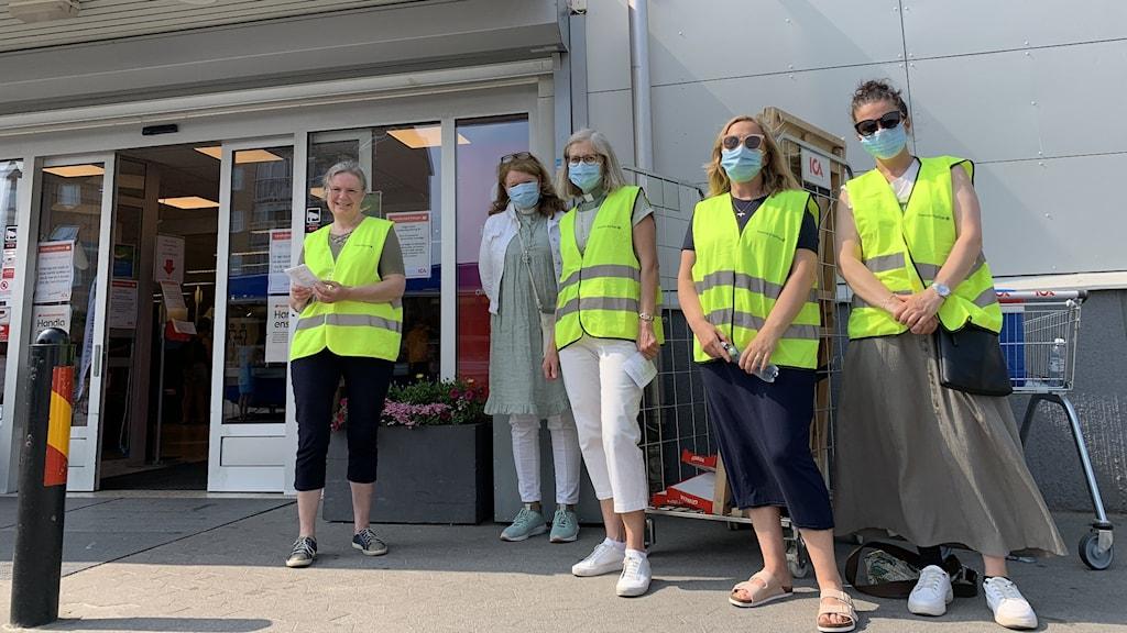 Fem kvinnor, fyra av de i reflexvästar och fyra med munskydd står utanför entrén till en mataffär.