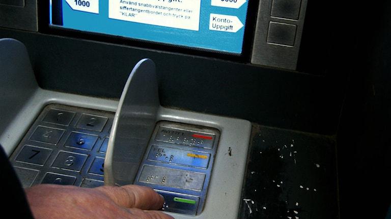 Man tar ut pengar från en bankomat. Foto: Hasse Holmberg/Scanpix