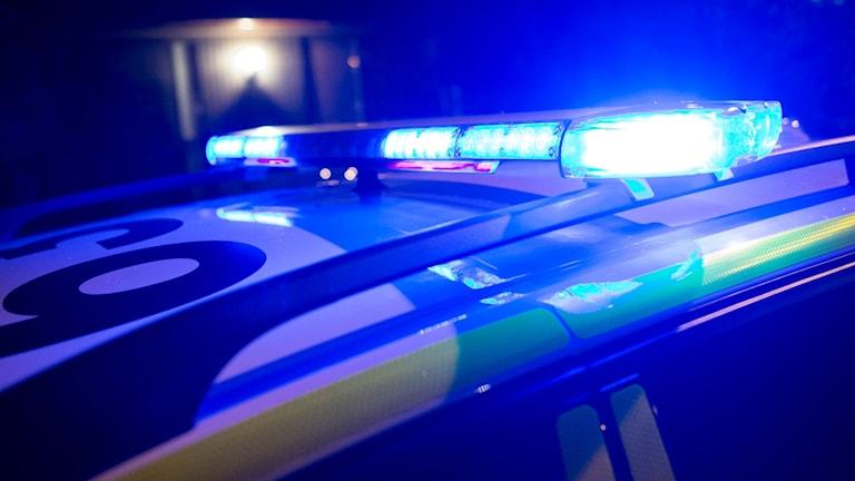 En polisbils blåljus i mörker.