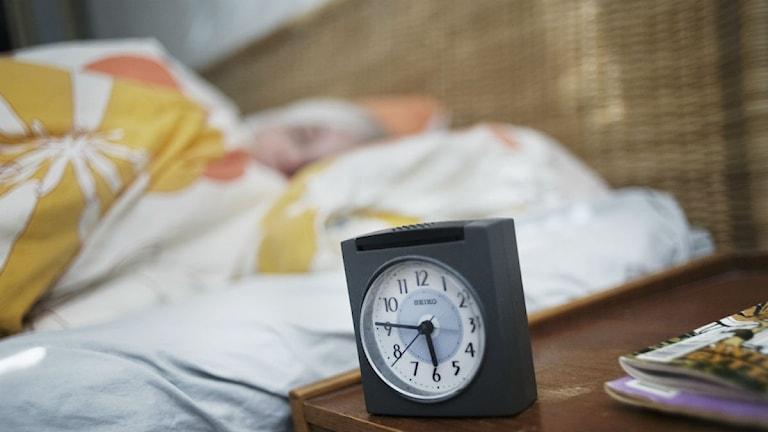 Kvinna som sover i säng bredvid väckarklocka.