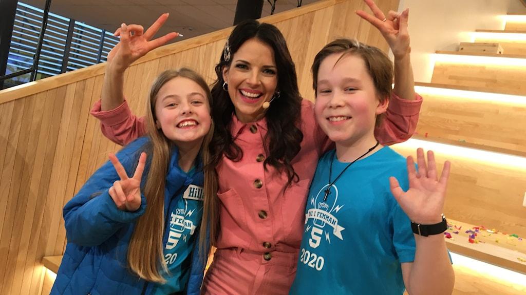 Hilla Lilja och Axel Jungermann från Nova Montessoriskola tillsammans med programledaren Malin Olsson i riksfinalen av Vi i femman.
