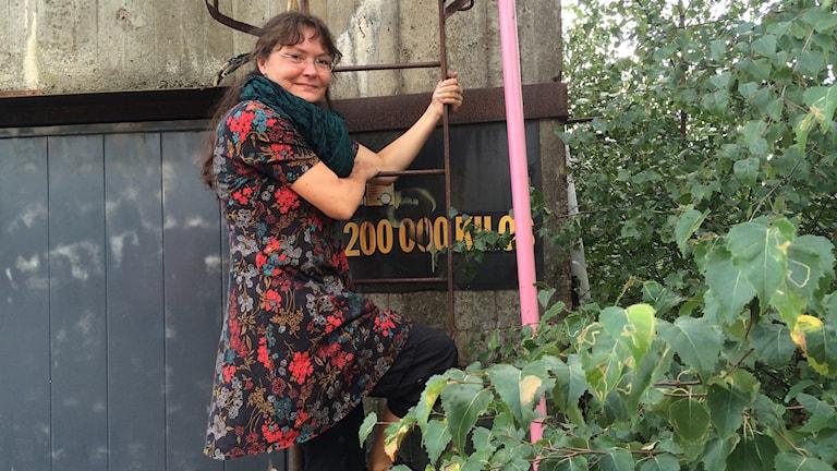 Ann-Louice Liljedahl står på en stege som leder upp till kranen.