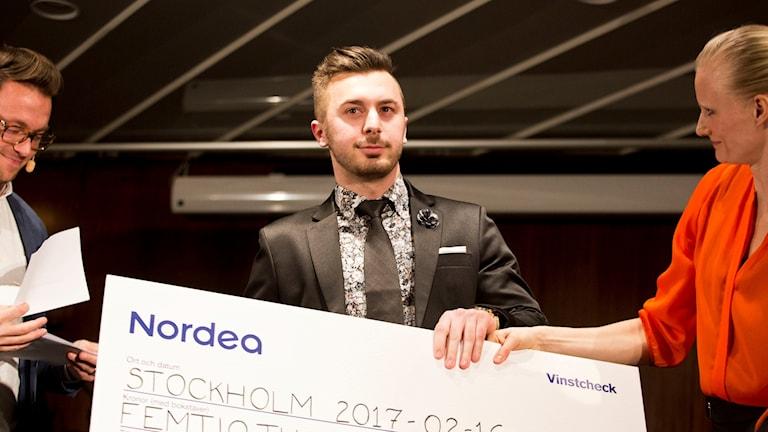 Adnan Bainca från Unite people i Varberg håller i en stor check som han får för sitt arbete med att integration genom fotboll i Varberg. Foto: Evelina Carborn.