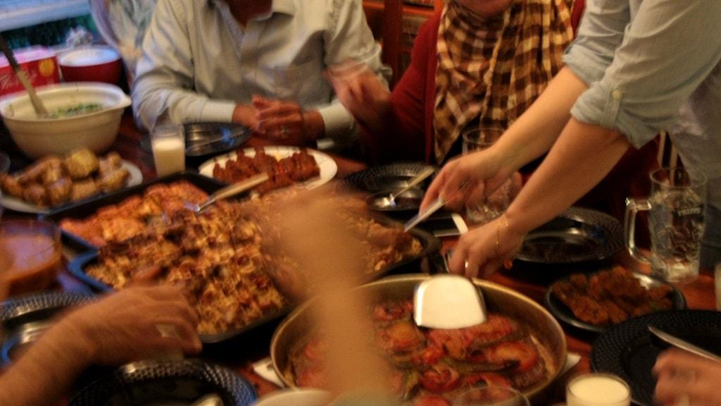 En bild på människor som sitter runt ett bord och äter mat.