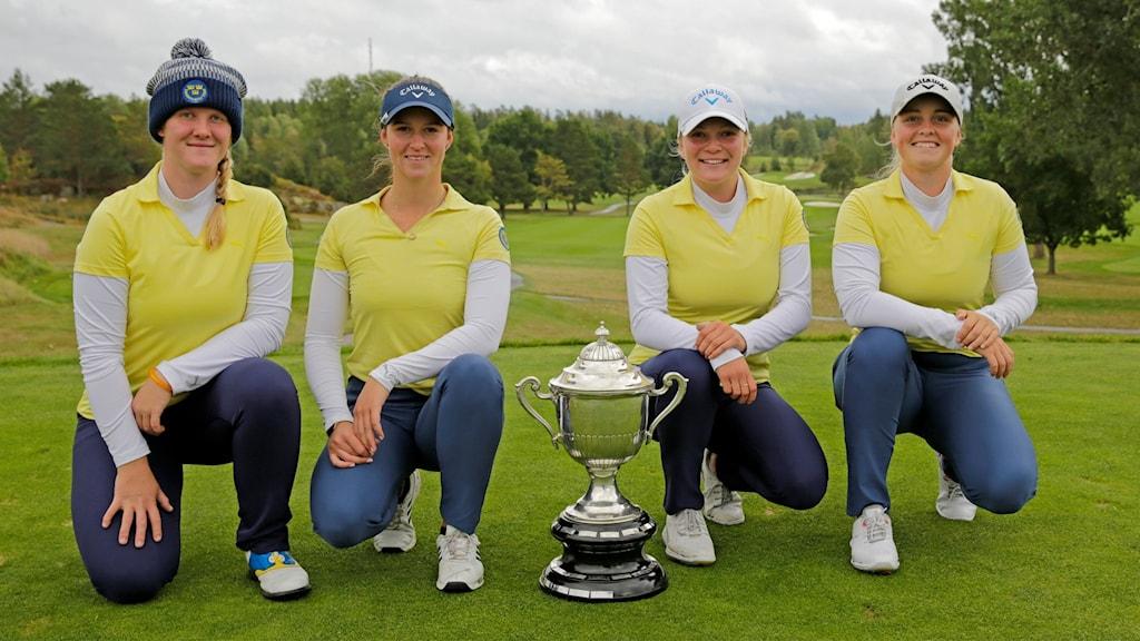 Tre kvinnor står på ett knä vid en pokal på en golfbana.