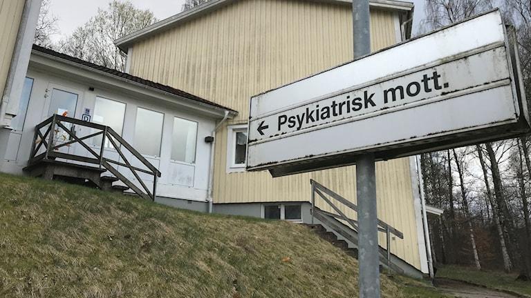 """Skylt med texten """"Psykiatrisk mottagning"""" som pekar mot en dörr i en gul byggnad. Foto: Therese Wahlgren/Sveriges Radio."""