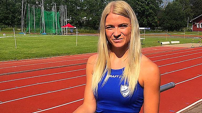 Elin Larsson står på en friidrottsplan.