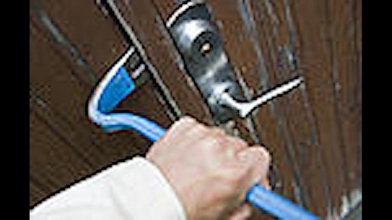 En inbrottstjuv bryter upp en dörr med kofot