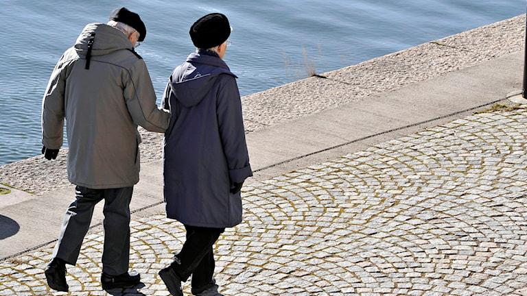 Ett äldre par promenerar i vårsolen. Foto Hasse Holmberg /SCANPIX