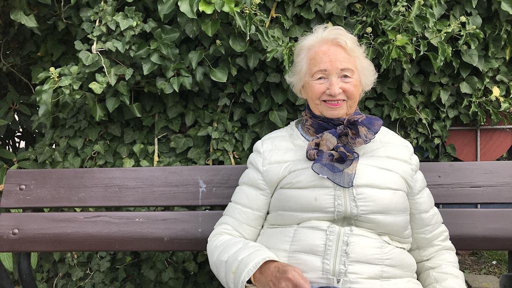 Lilly Eriksson sitter på en parkbänk. Hon har kort, vitt hår och är klädd i en vit dunjacka och mönstrad sjal.