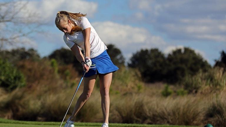 En ung kvinna spelar golf