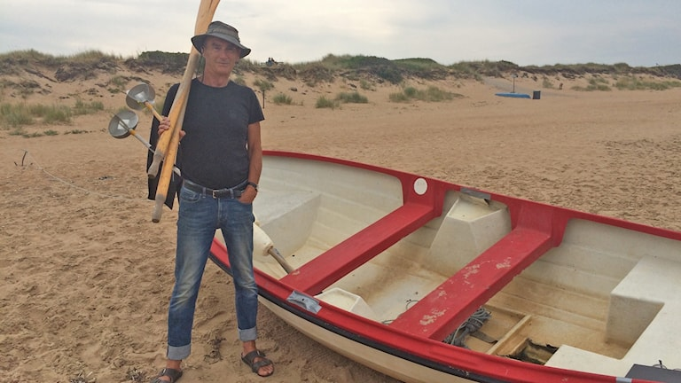 Christer Hansson som är fritids- och husbehovsfiskare står på en strand bredvid en båt och håller två åror över ena axeln.