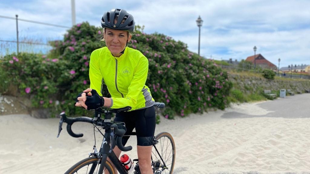 En kvinna ståendes på en cykel, iklädd neongul tröja, cykelhjälm och sportbyxor framför Varbergs fästning och tittar in i kameran
