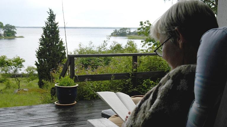 Kvinna sitter och läser en bok.