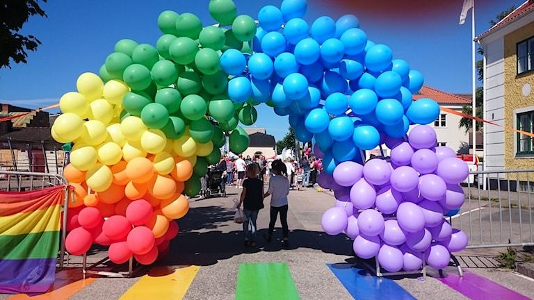 Två små barn går under en regnbåge av ballonger.