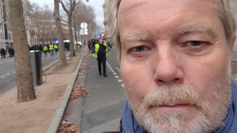 Journalisten Johan Tollgerdt i förgrunden och demonstranter/gula västar och poliser i bakgrunden.