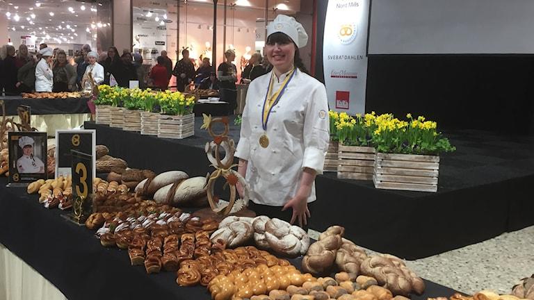 Pernilla Boström står bakom en länga med olika bakverk. Hon har en medalj om halsen och är iklädd bagarkläder.
