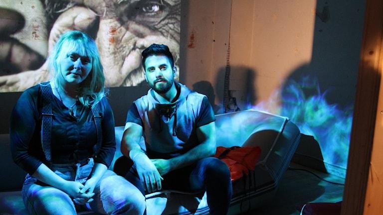 Lotta & Ahmed sittandes i en soffa framför videoprojecering av kvinna.