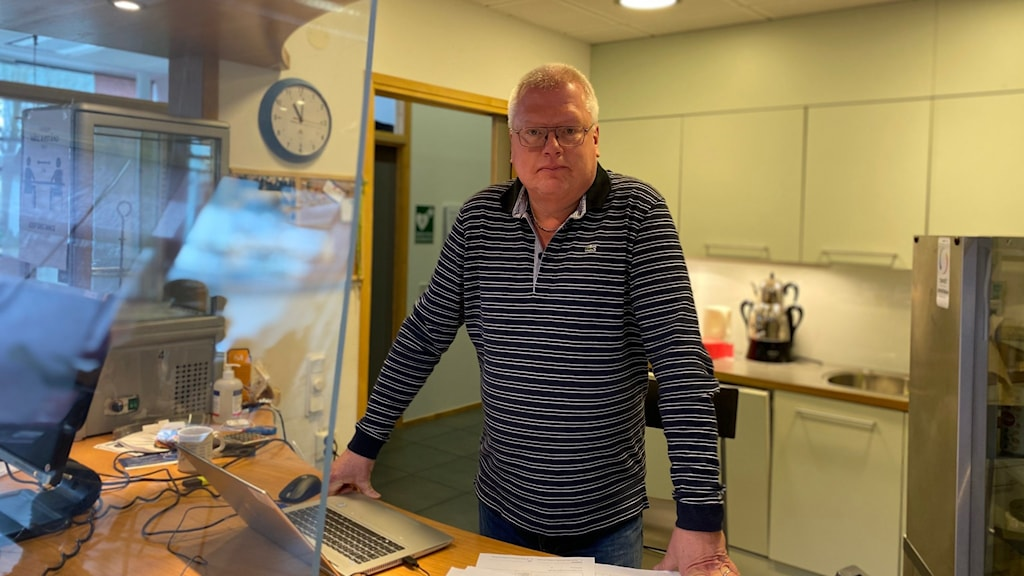 Bakom plexiglas och ett skrivbord med laptop och papper står en man med händerna mot skrivbordet och lutar sig fram. Han har kort grått hår, glasögon, en svartvitrandig tröja och tittar in i kameran.