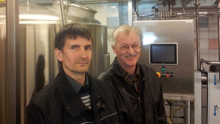 Fr v Lennart Svenäng och Bengt Erlandsson framför de nya mjölktankarna på Källsjö mejeri. Foto: Magnus Hagström/Sveriges Radio