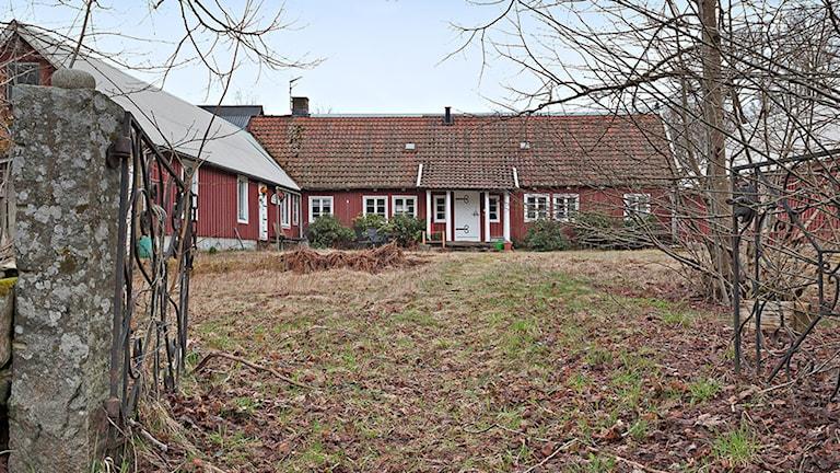 Fastighet i Snorrslida som är ute till försäljning. Ett rött hus med vita knutar. I förgrunden syns en grind.
