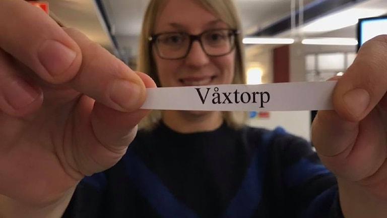Reporter Lina Millberg håller upp en liten lapp med texten Våxtorp på.