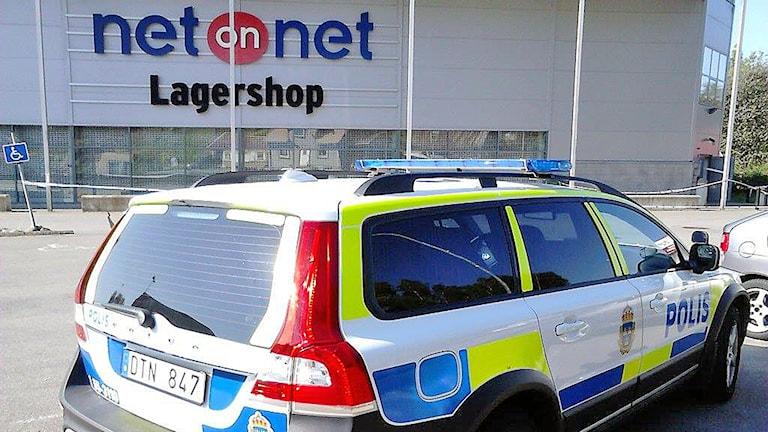 En polisbil står i förgrunden framför en butiksbyggnad