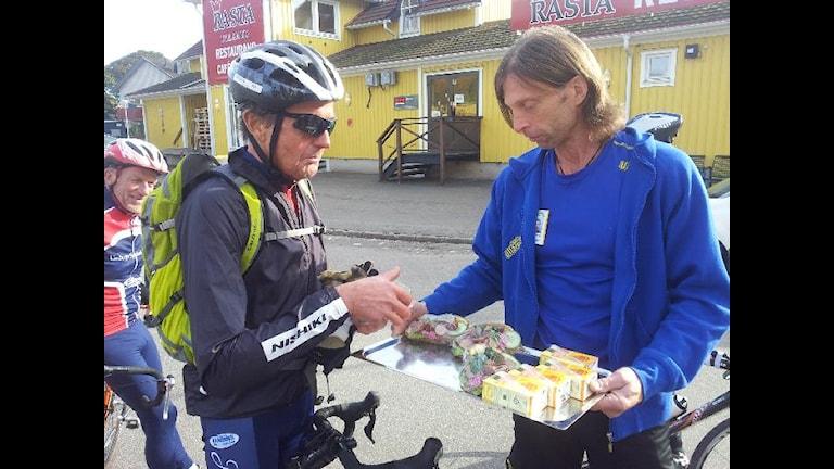 Ola-Conny bjuder våra cyklister på specialmackor. Foto: Sveriges Radio